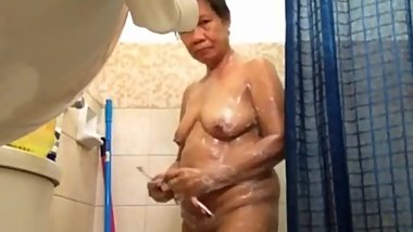 Old, chubby, Filipino woman in shower on cam.