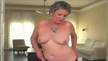 Grandma Sandora with short hair masturbates then has sex on a chair.